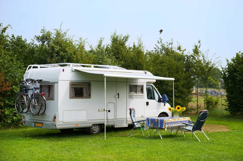 Mobile Caravan With Retractable Awning And Picnic Table At Campsite