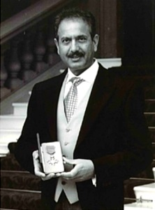 Pete Rana Holding MBE Award From Her Majesty The Queen