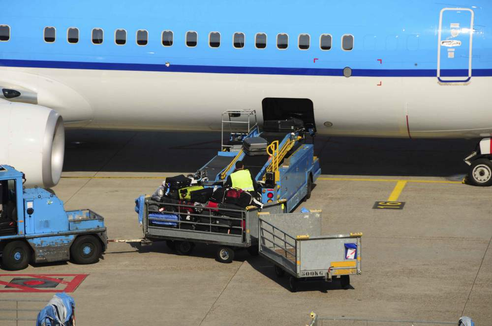 Airport Workers Loading Baggage And Luggage Onto A Large Aeroplane